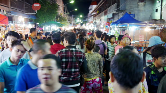 Many people making their way through at night market in Thailand