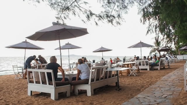 vidéos et rushes de de nombreuses personnes, salon et salle à manger sur une plage tropicale en face de l'océan - littoral