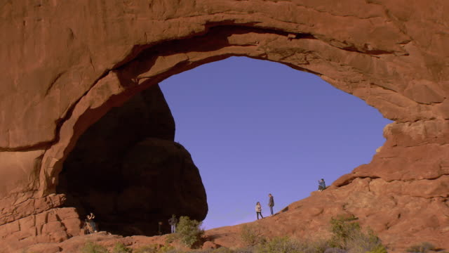 Many people standing within a massive sandstone arch called North Window in the spectacles area
