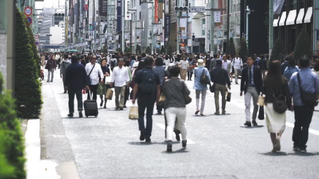 東京の銀座のメイン通りを歩いて多くの人々 - 土曜日点の映像素材/bロール