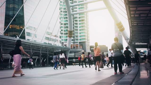 Many people walking on the sidewalk