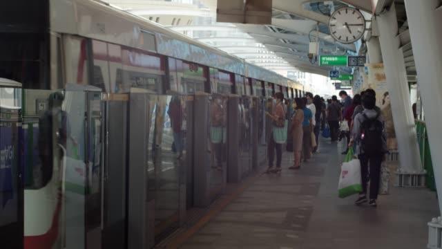 vidéos et rushes de beaucoup de gens portant le masque de visage attendant le train à la plate-forme de train de ciel, bangkok. - quai de gare