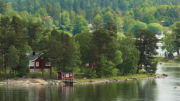 Many Red Swedish Wooden Sauna Logs Cabins Houses On Island Coast In Summer Cloudy Day