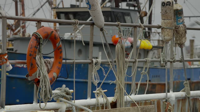 Many ropes and buoys hanging on rail of fishing boat