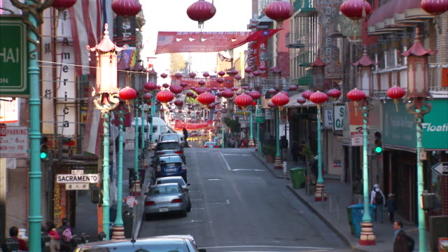 many rows of red paper lanterns hanging on wire across street, revealing sloped road, mid-rise buildings w/ store signs, unidentifiable pedestrians,... - chinatown stock videos & royalty-free footage