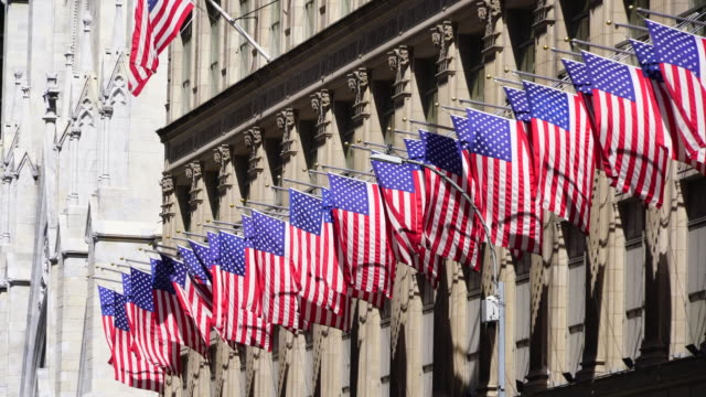 many shaking american flags at saks fifth avenue at midtown manhattan new york ny usa on apr 22 2018. - st. patrick's cathedral manhattan stock videos and b-roll footage
