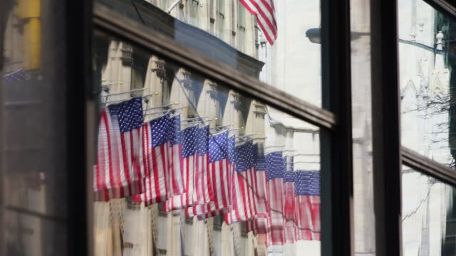 many shaking american flags at saks fifth avenue, which reflect to the building windows at midtown manhattan new york ny usa on apr 22 2018. - st. patrick's cathedral manhattan stock videos and b-roll footage