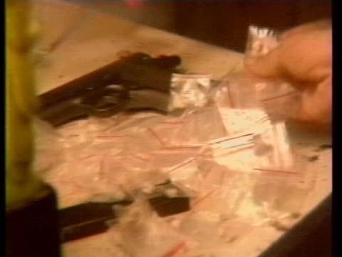 stockvideo's en b-roll-footage met many small baggies of crack-cocaine are spread across a table along with a handgun. - crime or recreational drug or prison or legal trial
