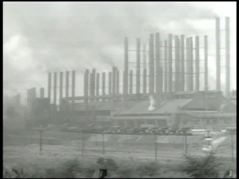 stockvideo's en b-roll-footage met many smoke stacks in industrial building possibly steel mill munitions white smoke pouring from industrial building w/ smoke stacks grouping of smoke... - munitie