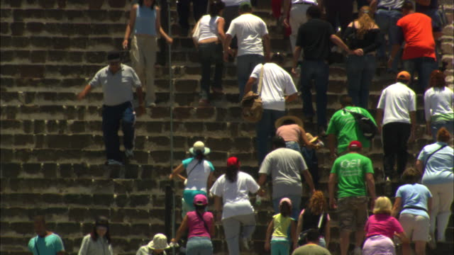 Many tourists walk up and down the steps at the Pyramid of the Sun.
