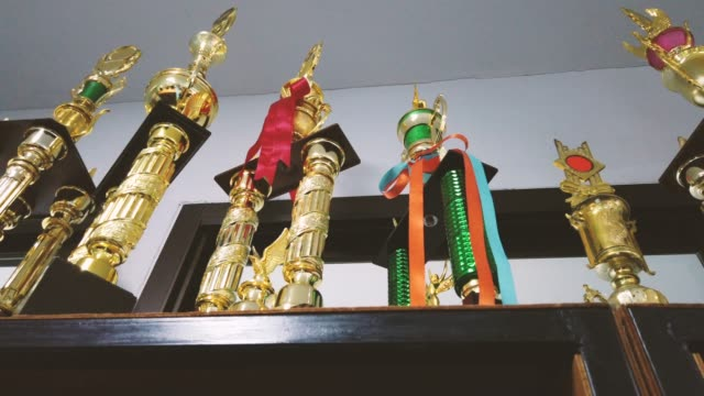 many trophies on the wood showcase. comparable to life reward - trophy stock videos & royalty-free footage