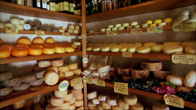Many varieties of cheese line the shelves of a Tuscany market.