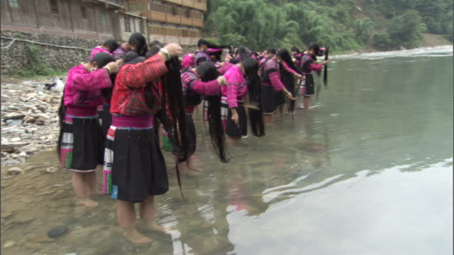 many women stand side-by-side and wash their long hair in a river. - combing stock videos & royalty-free footage