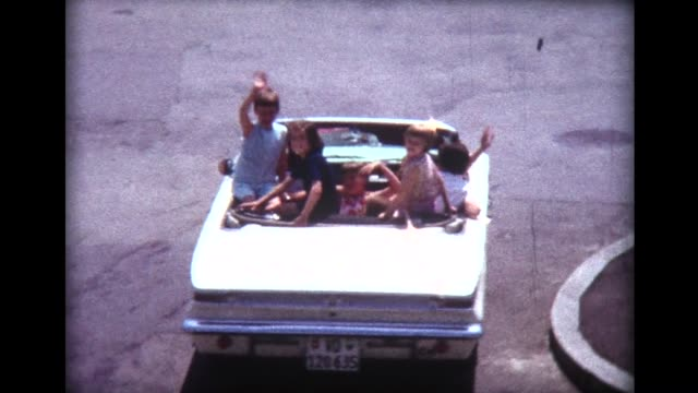 1966 many young girls in open convertible drive away (with no seat belts) - auto convertibile video stock e b–roll