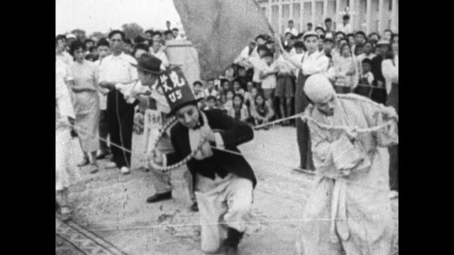 mao and zhou enlai laugh as acrobats dressed as western caricatures perform for children. - mao tse tung video stock e b–roll