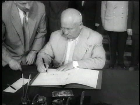 Mao Tse Tung and Nikita Khrushchev sign documents and shake hands