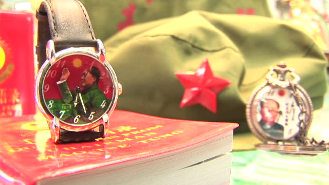CU Mao watch on top of book, next to Communist hat in Tiananmen Square gift shop/ Beijing, China