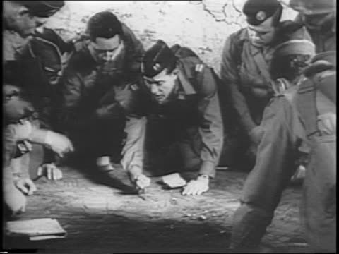 map of europe with a wall around germany and northern france / zoom in on officer surrounded by crouched soldiers pointing at map with a pencil /... - fallschirmjäger stock-videos und b-roll-filmmaterial