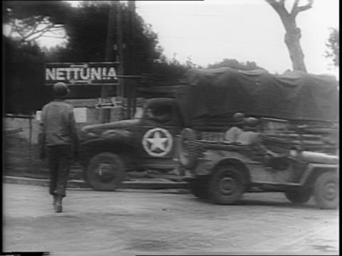 map of no mans land in italy / pan showing anzio beach / montage of troops arriving with duffle bags on shoulders, army vehicles and troops in... - arrivo video stock e b–roll