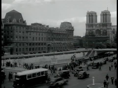 vidéos et rushes de map of paris. ext busy paris street cars pedestrians notre dame bg. man sitting & writing at outdoor cafe street bg . three men standing talking... - 1939