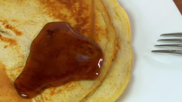 vídeos de stock, filmes e b-roll de cu maple leaf syrup being poured over pancakes  - xarope