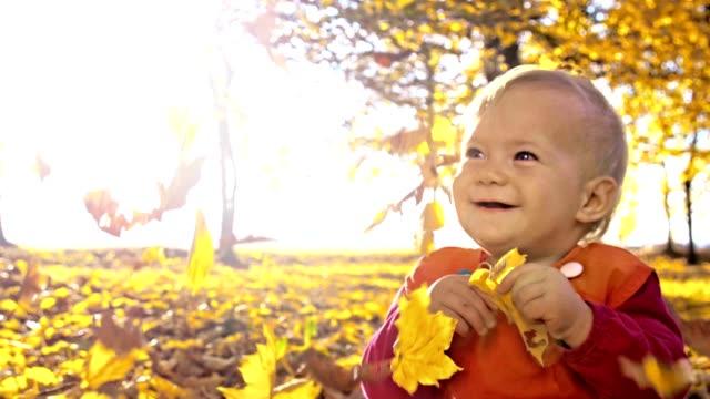 SLO MO lönn löv faller över baby flicka