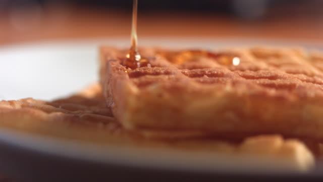 vídeos y material grabado en eventos de stock de cu slo mo maple syrup being poured on waffle top from above / manchester, united kingdom - waffles