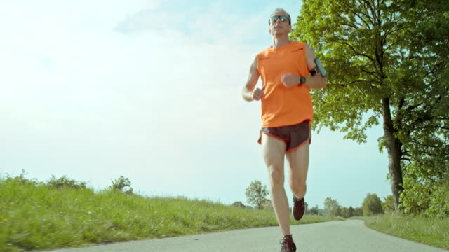 slo mo ts marathon runner running on a sunny day - marathon stock videos and b-roll footage