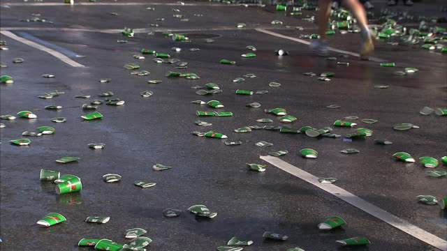 marathon runners jog and walk past empty water cups on a wet street. - pampering self stock videos and b-roll footage