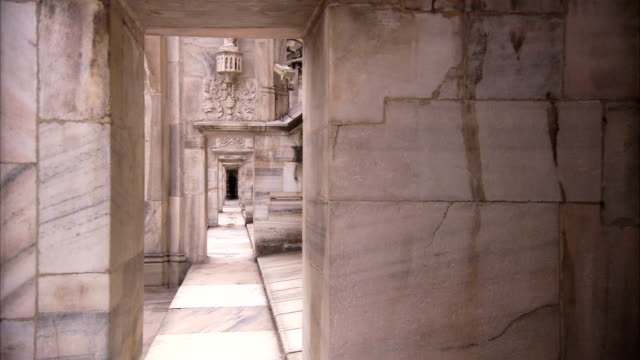 marbled stone archways lead down a long corridor of the milan cathedral. available in hd. - cathedral stock videos & royalty-free footage