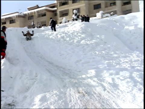 march 1, 2005 sportsmen sledding down a hill while a crowd cheers them on / tehran, iran - 水の形態点の映像素材/bロール