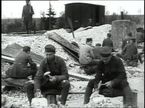 vídeos de stock e filmes b-roll de march 12 1919 ws german prisoners hammering on rock pile / neufchateau vosges france - 1919