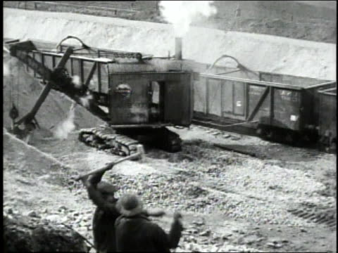 vidéos et rushes de march 12 1919 ws men swinging hammers with big mechanical steam shovel digging and loading train cars with sand in background / neufchateau vosges... - 1910 1919