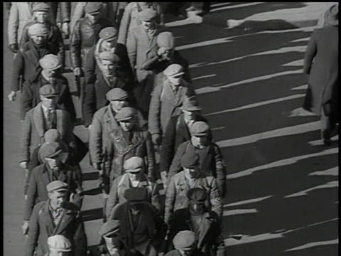 march 13 1938 bw civilians marching through pedestrian traffic wearing swastika armbands / vienna austria - anno 1938 video stock e b–roll