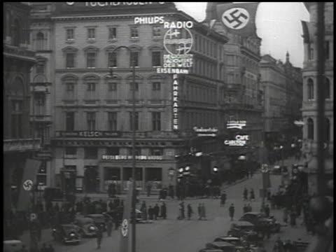 march 13 1938 bw street scene showing 'philips radio' neon sign with huge swastika flag hanging behind it / vienna austria - hakenkreuzfahne stock-videos und b-roll-filmmaterial