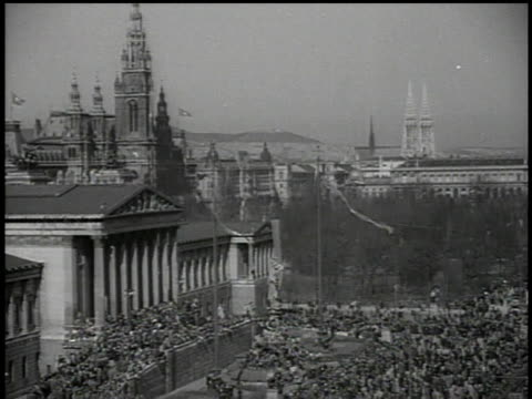 vídeos y material grabado en eventos de stock de march 13 1938 bw thousands of people crowding the square before the rathaus and parliament buildings decorated with hanging nazi flags / vienna... - 1938
