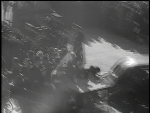 march 13, 1938 bw truck carrying civilians waving swastika flags driving through the street / vienna, austria - insignier bildbanksvideor och videomaterial från bakom kulisserna
