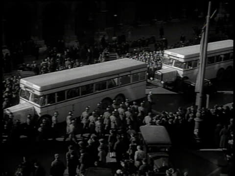 stockvideo's en b-roll-footage met march 13 1938 ha german army unit falling into formation and marching past row of buses and civilians / vienna austria - 1938