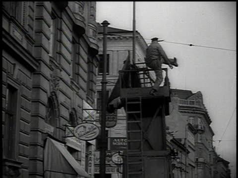 vidéos et rushes de march 13 1938 la men climb onto platform to hang swastika flag / vienna austria - vienne autriche