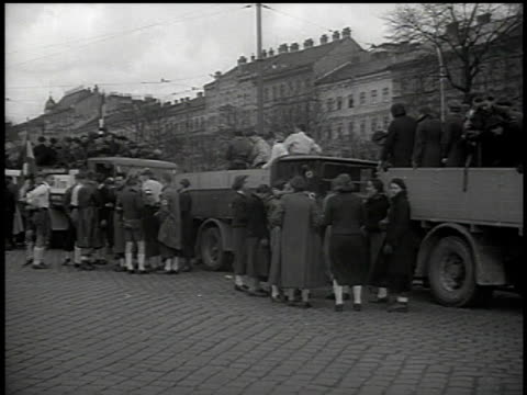 march 13, 1938 montage boys and girls on street congregating for parade, some jumping down from back of trucks, some carrying swastika flags /... - 1938 stock videos & royalty-free footage
