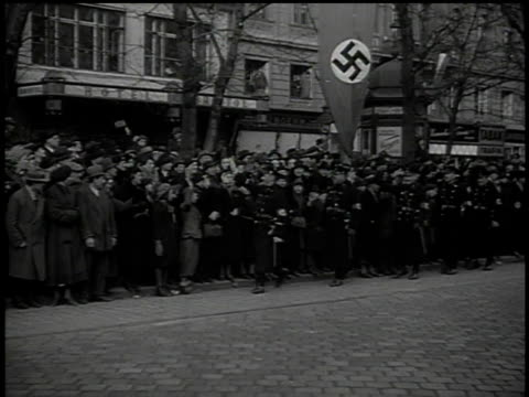 stockvideo's en b-roll-footage met march 13 1938 montage men in dark military dress uniforms walk along parade route giving the hitler salute / vienna austria - 1938