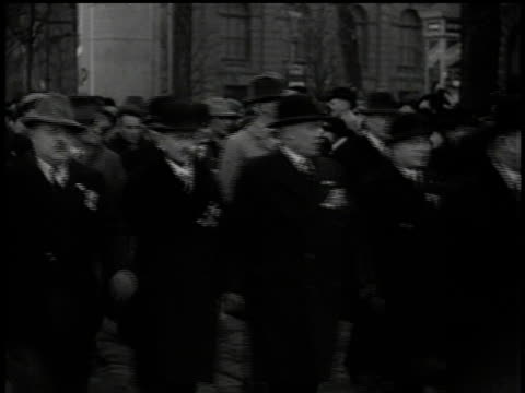 march 13, 1938 montage men in overcoats and bowler hats marching behind nazi banner some wearing medals / vienna, austria - 1938 bildbanksvideor och videomaterial från bakom kulisserna