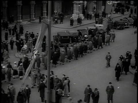 march 13 1938 ha parade of german army trucks and civilians beneath hanging swastika flags / vienna austria - hakenkreuzfahne stock-videos und b-roll-filmmaterial