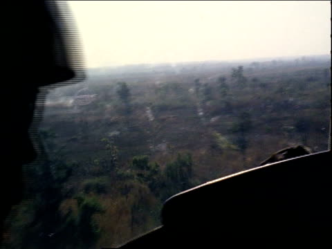 march 13, 1971 pilot flying a helicopter over a clearing / ho chi minh city, vietnam - 南ベトナム点の映像素材/bロール