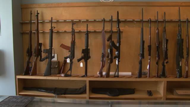 march 13 2008 pan display shelf holding rifles and shotguns / united states - gun shop stock videos & royalty-free footage