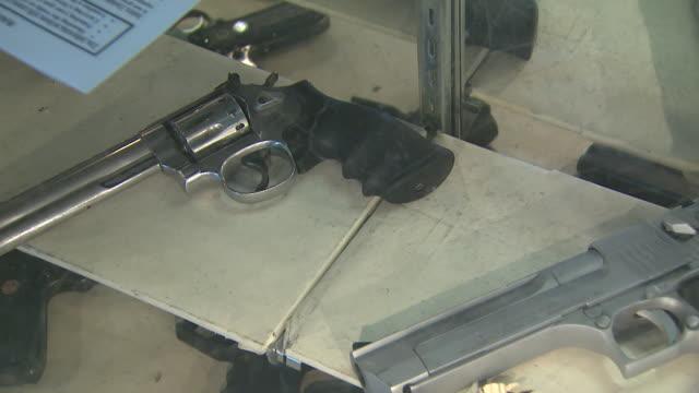 march 13 2008 pan handguns laying in display counter / united states - bordsyteinspelning bildbanksvideor och videomaterial från bakom kulisserna