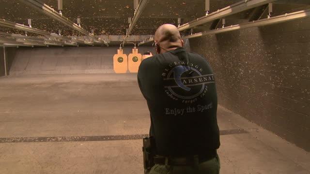 vídeos de stock e filmes b-roll de march 13, 2008 shooter firing pistol in target range with ear protection / united states - protetor de ouvido