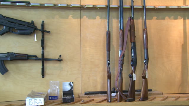 stockvideo's en b-roll-footage met march 13 2008 zi shotguns and assault rifles standing and hanging in display rack / united states - vuurwapenwinkel