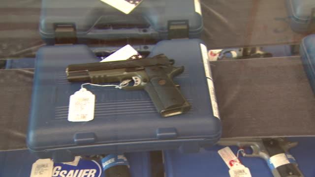 march 13, 2008 sig sauer pistols being displayed under glass / united states - skåp med glasdörrar bildbanksvideor och videomaterial från bakom kulisserna