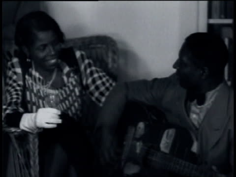 march 1935 ws leadbelly singing and playing guitar for a woman holding a wine glass / united states - 1935 stock videos & royalty-free footage